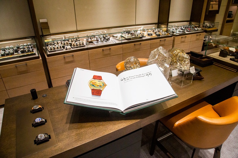 A large open book with information about timepieces is on displace at the central counter.