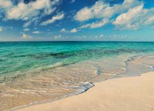 Clear tropical waters with many colors of blue & green. Rocks visible beneath the surf.