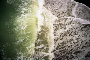 Opaque ocean water with only greens & yellows visible on the tops of waves.